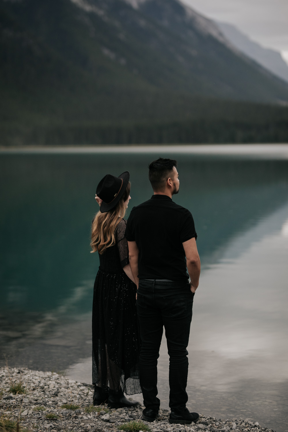 Boho Couple Dressed In Black Look At Turquoise Blue Lake In Canmore Alberta