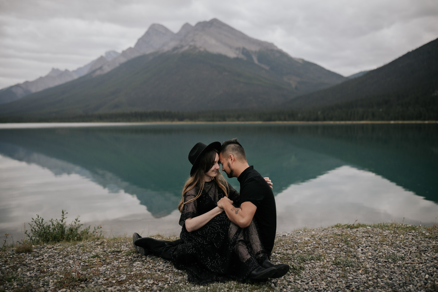Epic Photo Of Couple Sitting In Front Of Turquoise Blue Lake With Mountain In Background