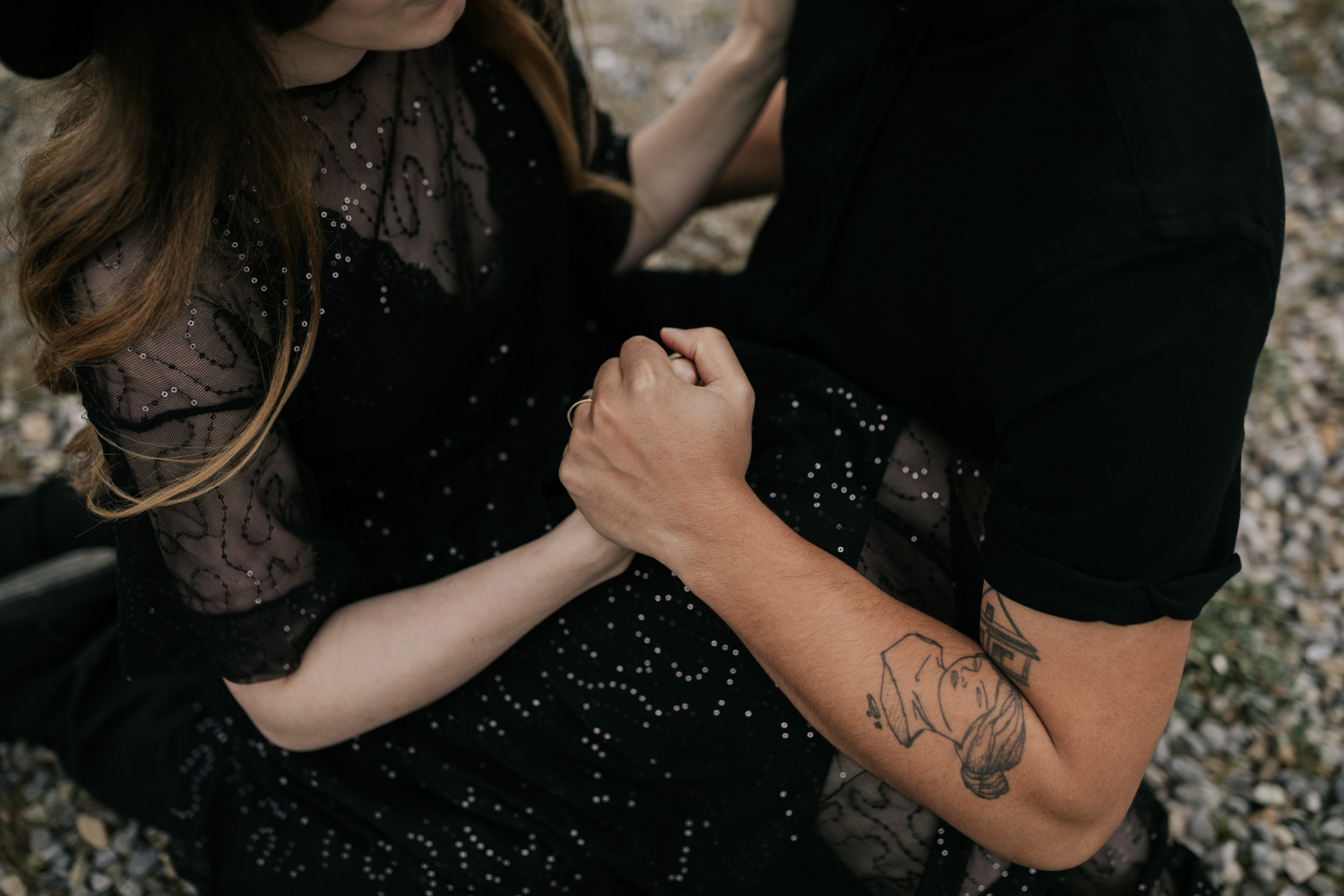Boho Couple Wearing Black With Tattoos Holds Hands