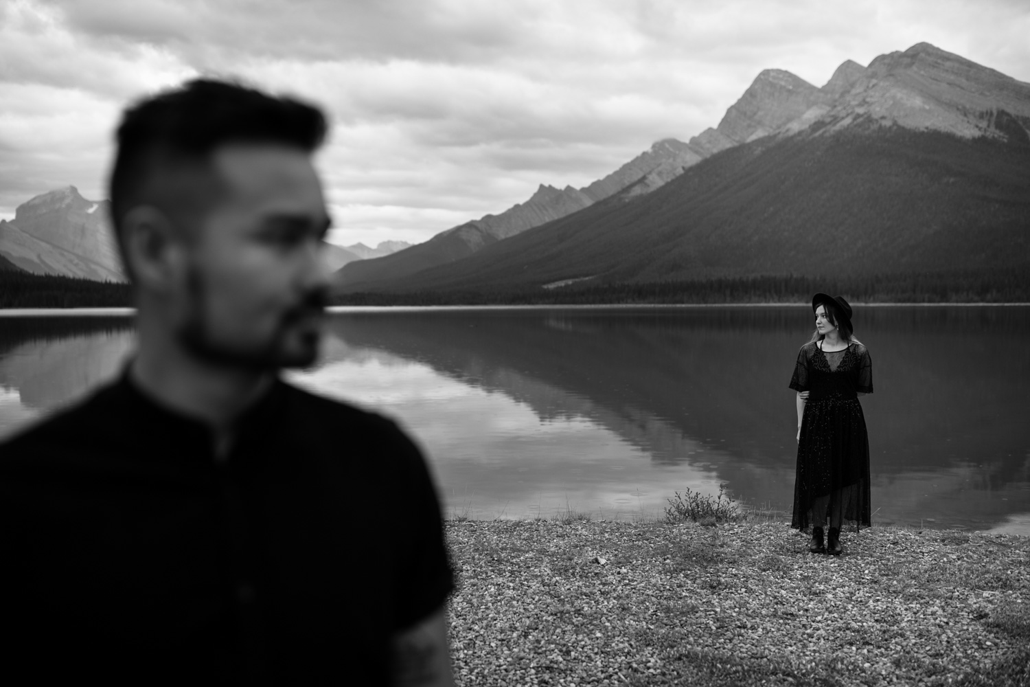 Engagement Shoot Photo Of Couple Standing In Front Of Goat Pond And Mountain Reflection