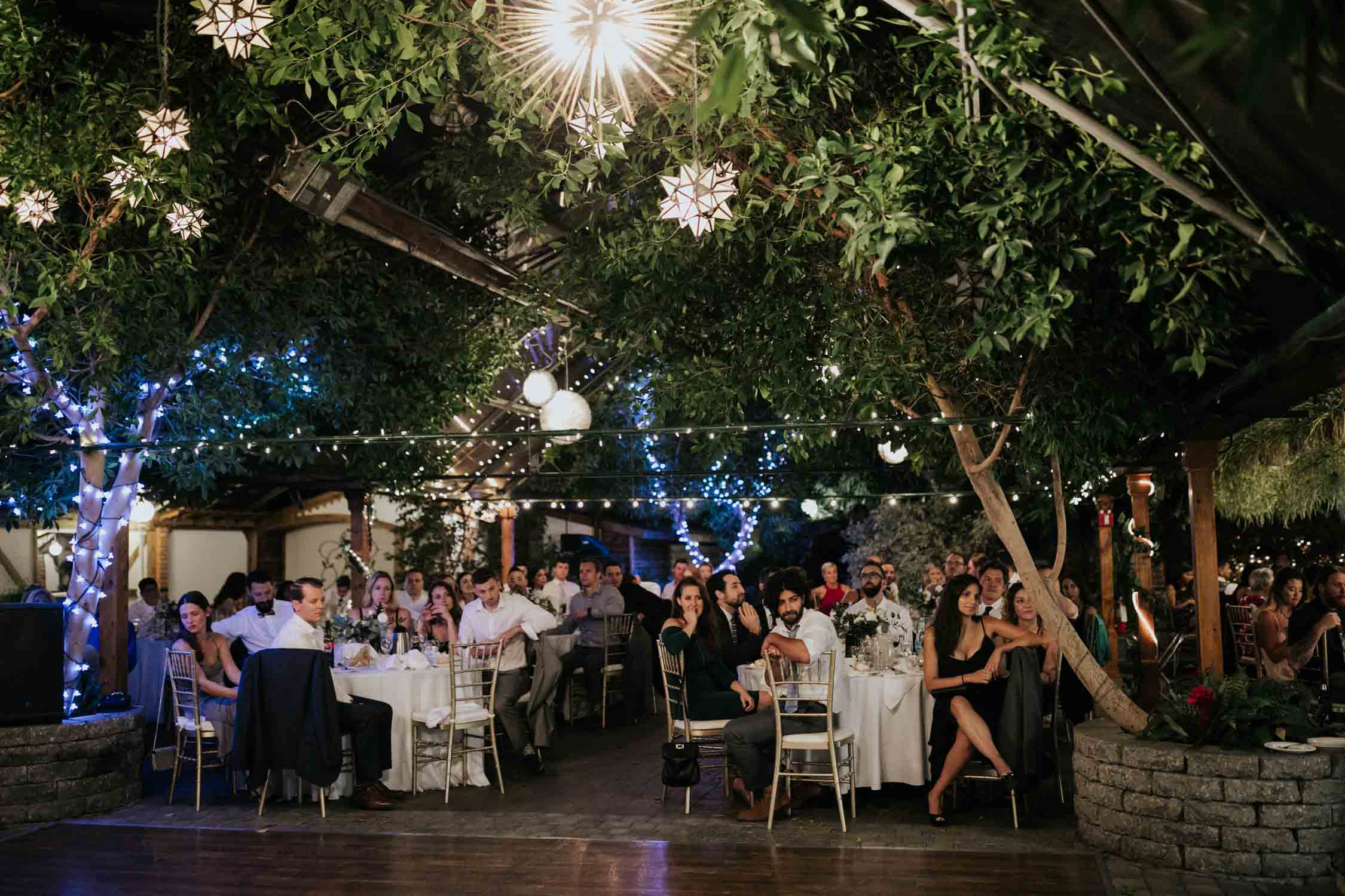 Guests during speeches at wedding reception at Madsen's Greenhouse wedding venue in Newmarket close to Toronto