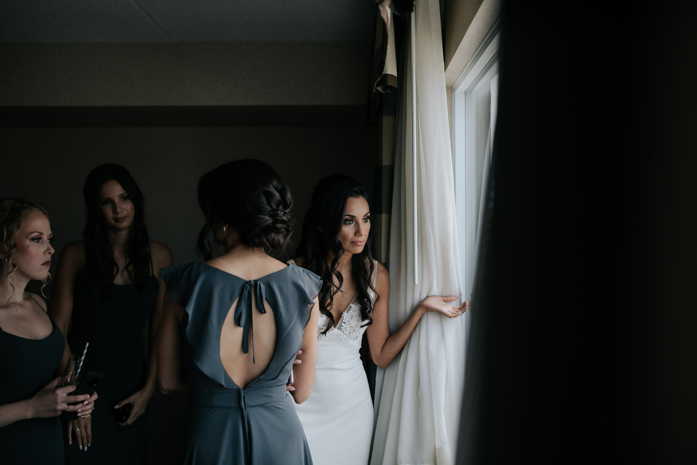 Natural non posed portrait of bride looking out window before Newmarket Wedding at Madsen's Greenhouse