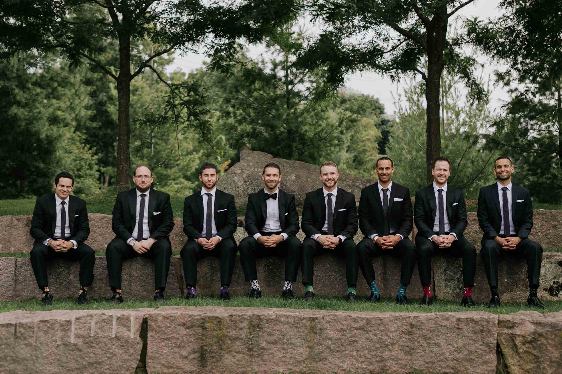 Fun portraits of groom and groomsmen with colourful socks at lake at Fairy Lake Park in Newmarket before wedding at Madsen's Greenhouse