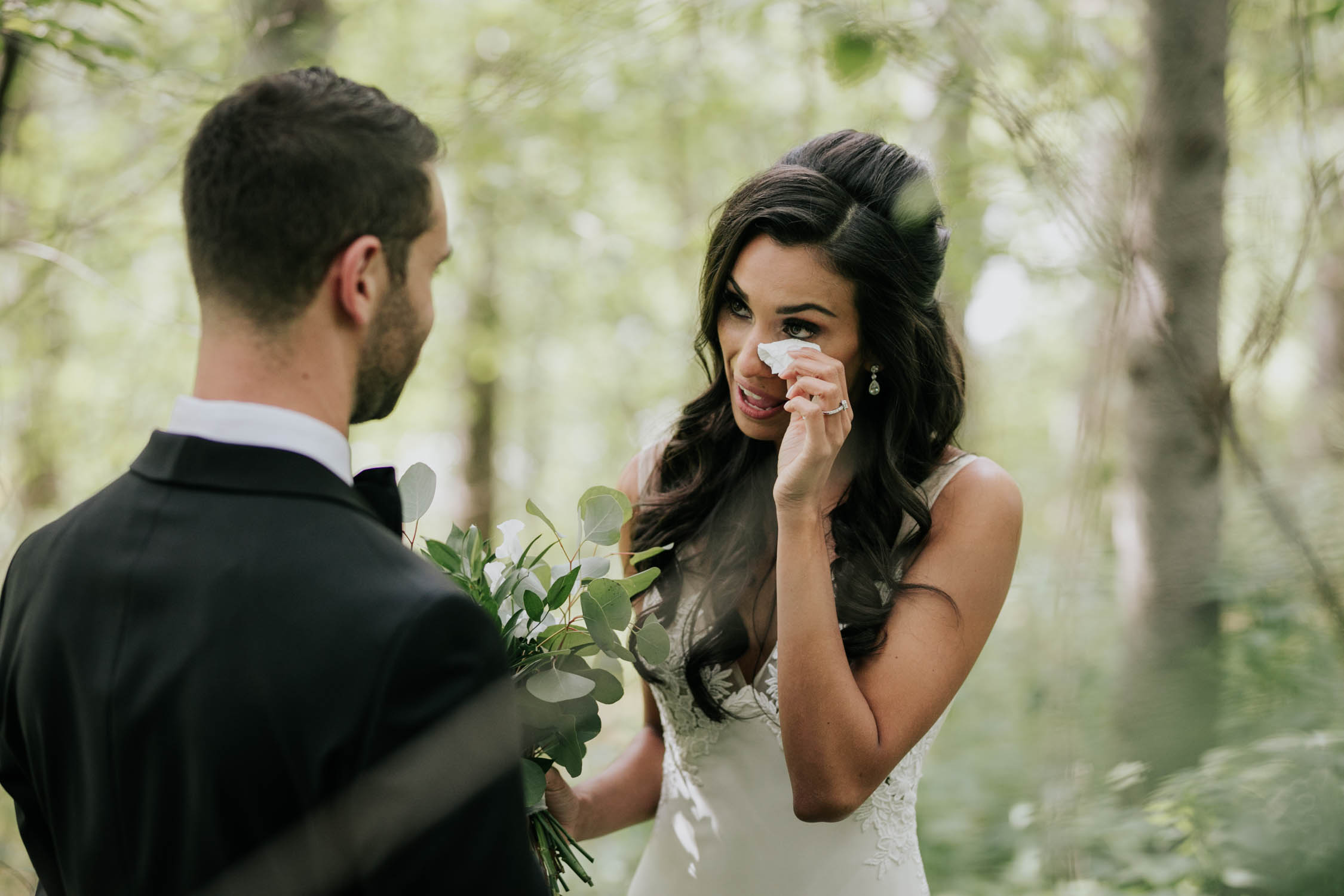 Bride crying as she sees her groom for the first time at their first look reveal in the forest at Fairy Lake Park in Newmarket before their wedding at Madsen's Greenhouse