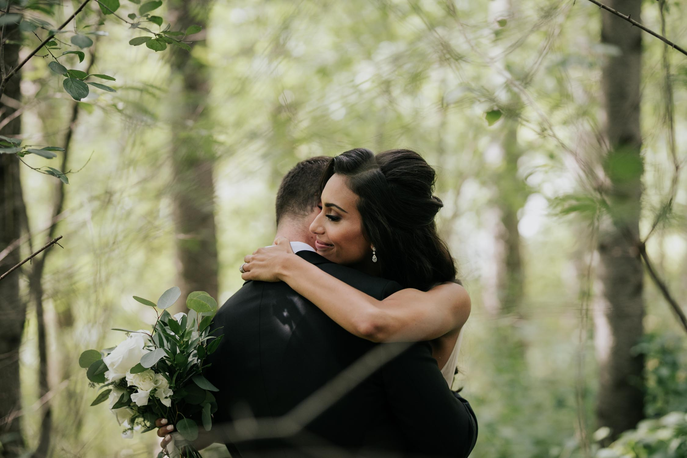 Bride hugging groom at their first look reveal in the forest at Fairy Lake Park in Newmarket before their wedding at Madsen's Greenhouse