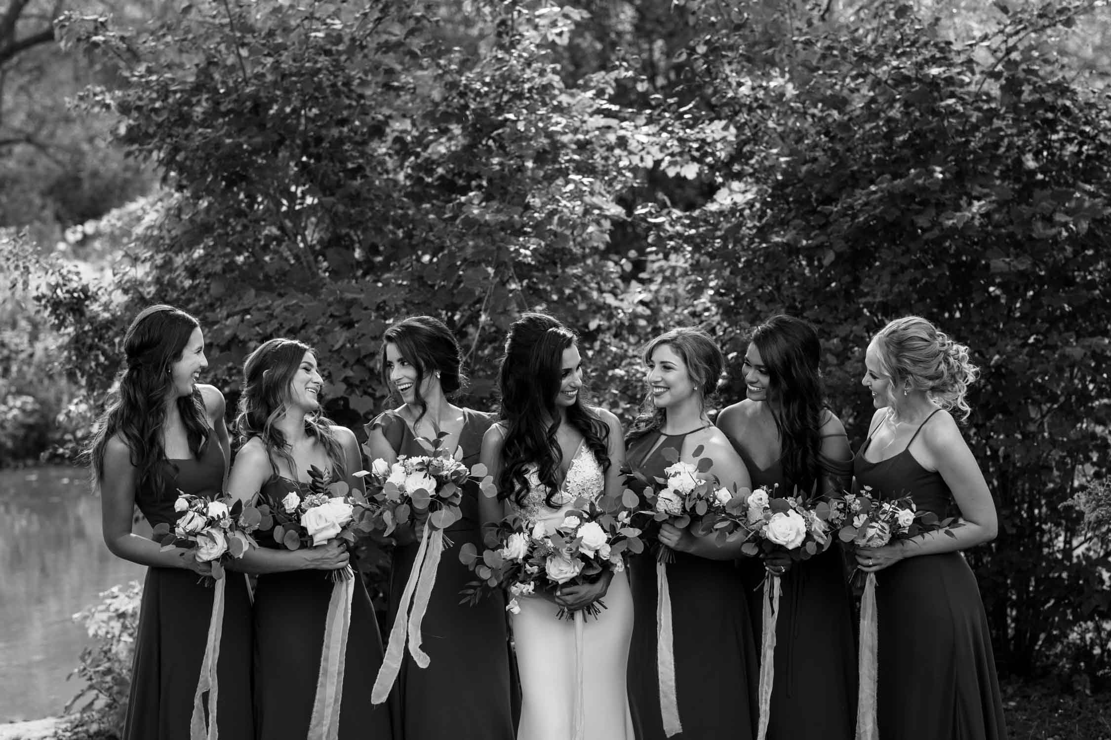 Candid and documentary style portraits of bride and bridesmaids at lake at Fairy Lake Park in Newmarket before wedding at Madsen's Greenhouse