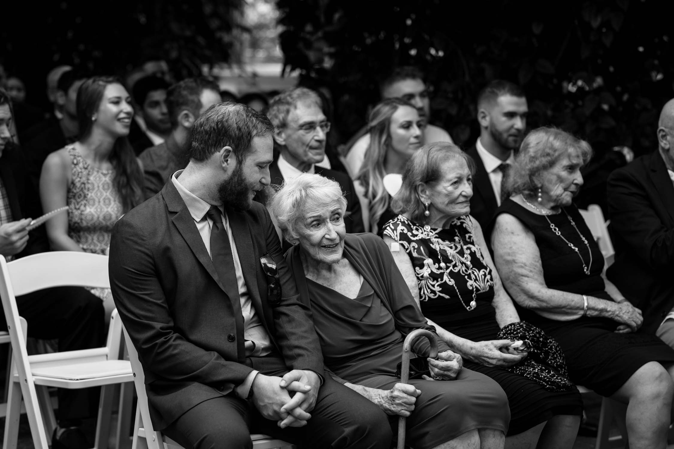 Candid photojournalistic photograph of grandmother during wedding ceremony at Madsen's Greenhouse wedding venue in Newmarket close to Toronto