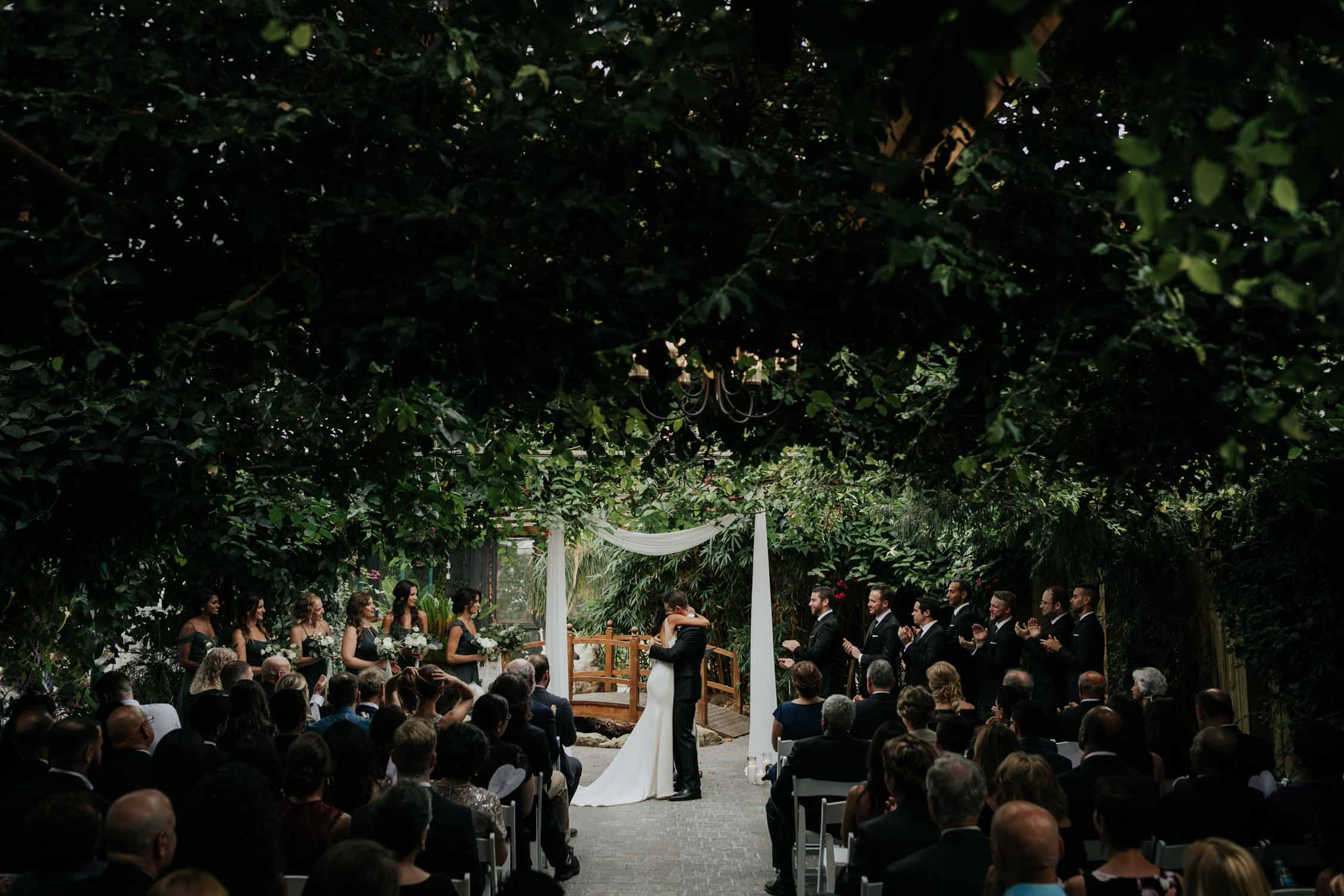 Emotional romantic moment after the first kiss of bride and groom hugging at at Madsen's Greenhouse wedding venue in Newmarket close to Toronto
