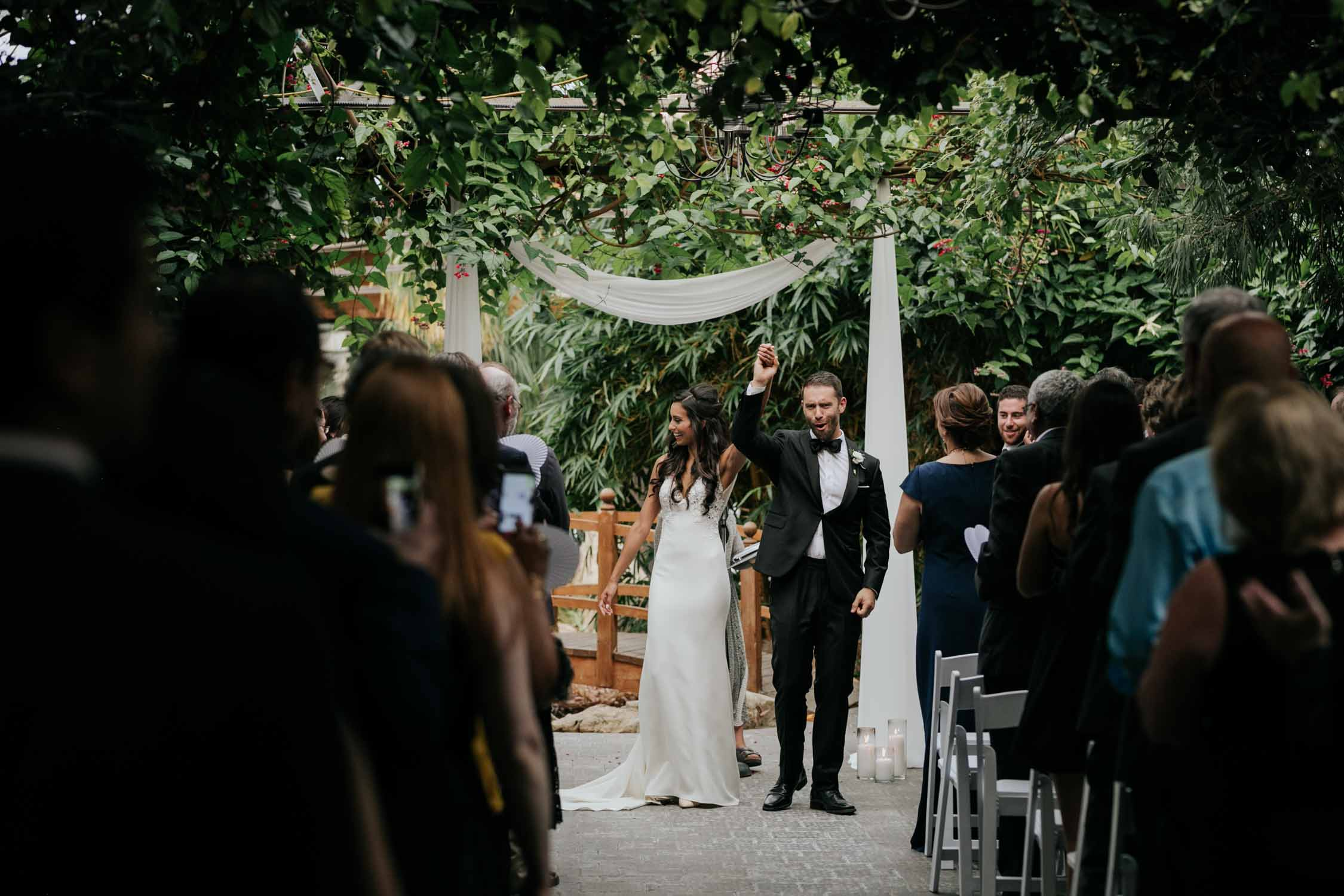 Happy joyful wedding photo of bride and groom walk down the aisle as everyone cheers them on at Emotional romantic moment after the first kiss of bride and groom hugging at Madsen's Greenhouse wedding venue in Newmarket close to Toronto