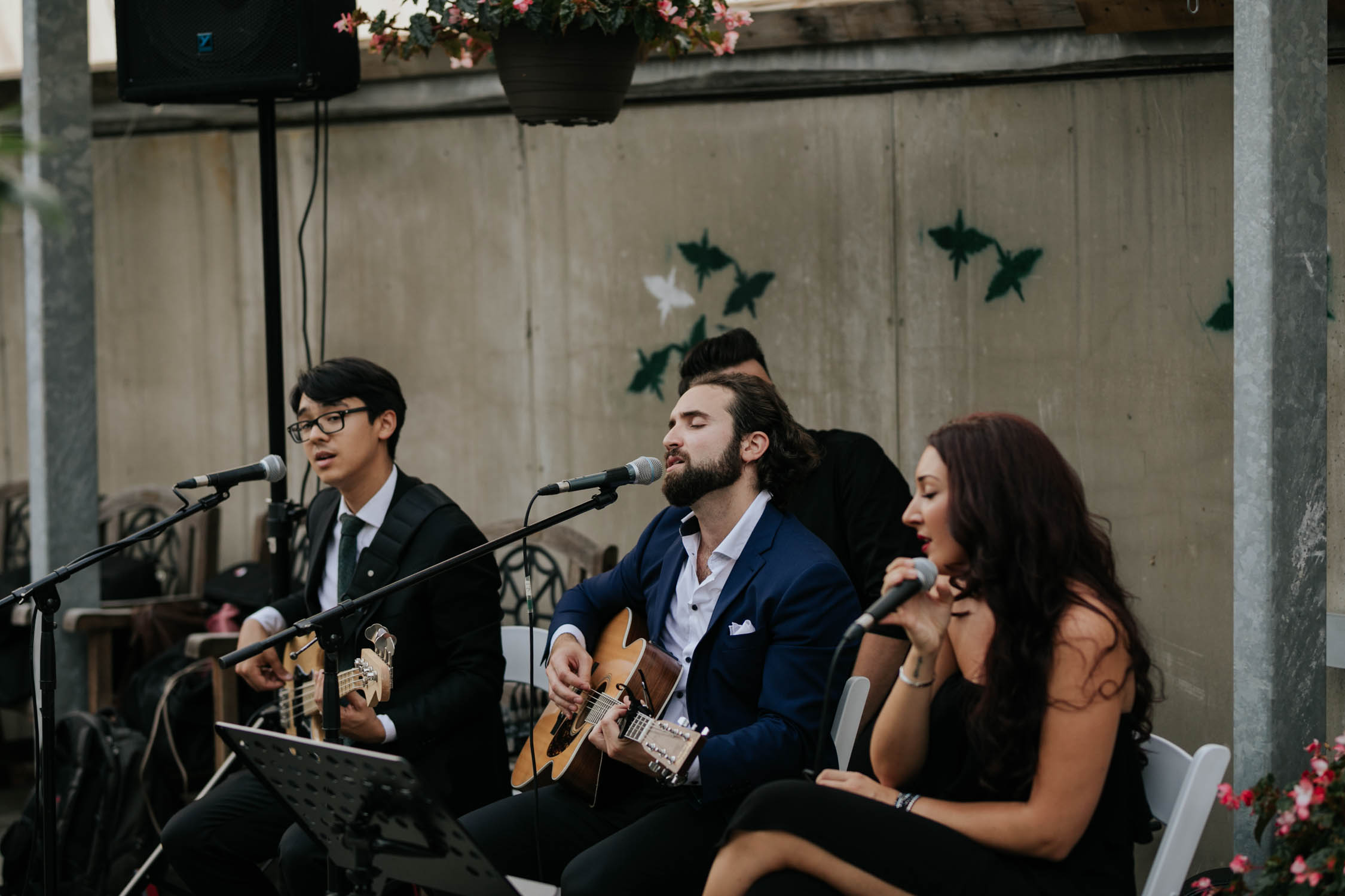 Luke Maxim, acoustic wedding band, sing during cocktail hour Candid and natural photographs of guests at Madsen's Greenhouse wedding venue in Newmarket close to Toronto