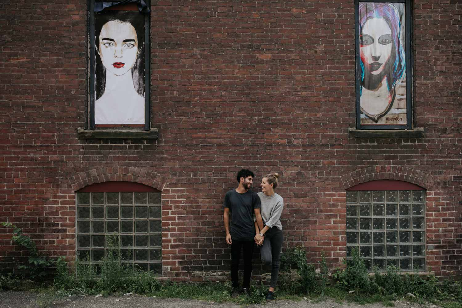 Fun and natural photo of couple standing in front of the brick wall of a historical building in St John, New Brunswick with art in the background