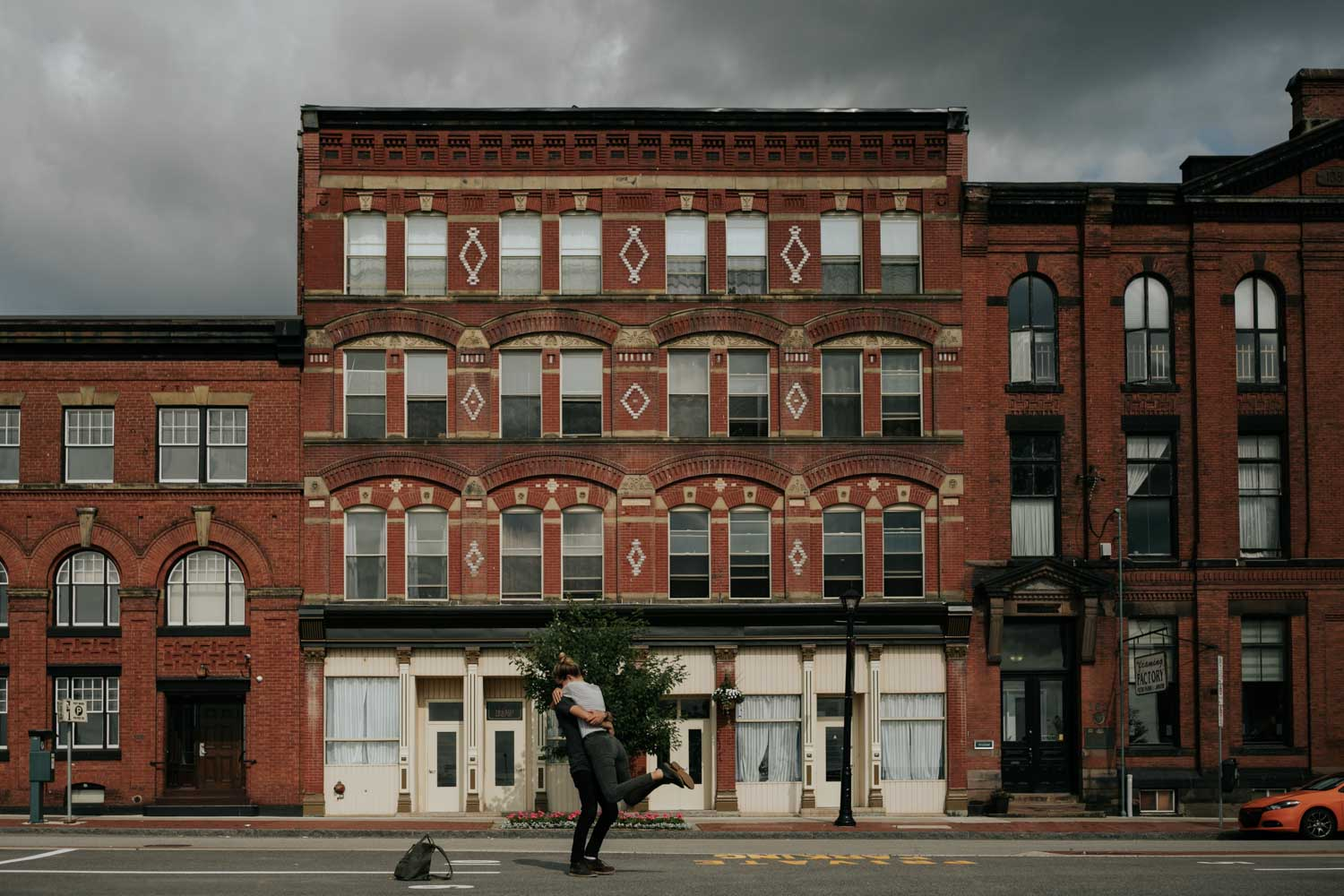 Husband spins wife around on the downtown streets of St John in New Brunswick in front of epic historical buildings
