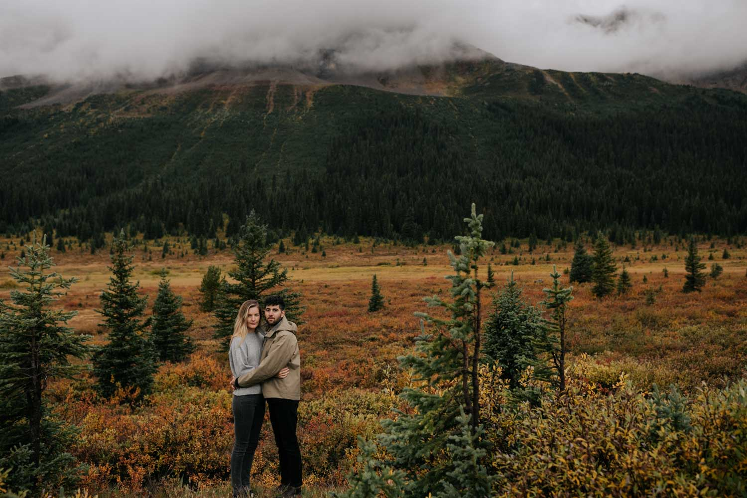 Wedding portrait session on the Icefield Parkway between Banff and Jasper, with Autumn tones in the field beyond and beautiful mountains surrounding the couple