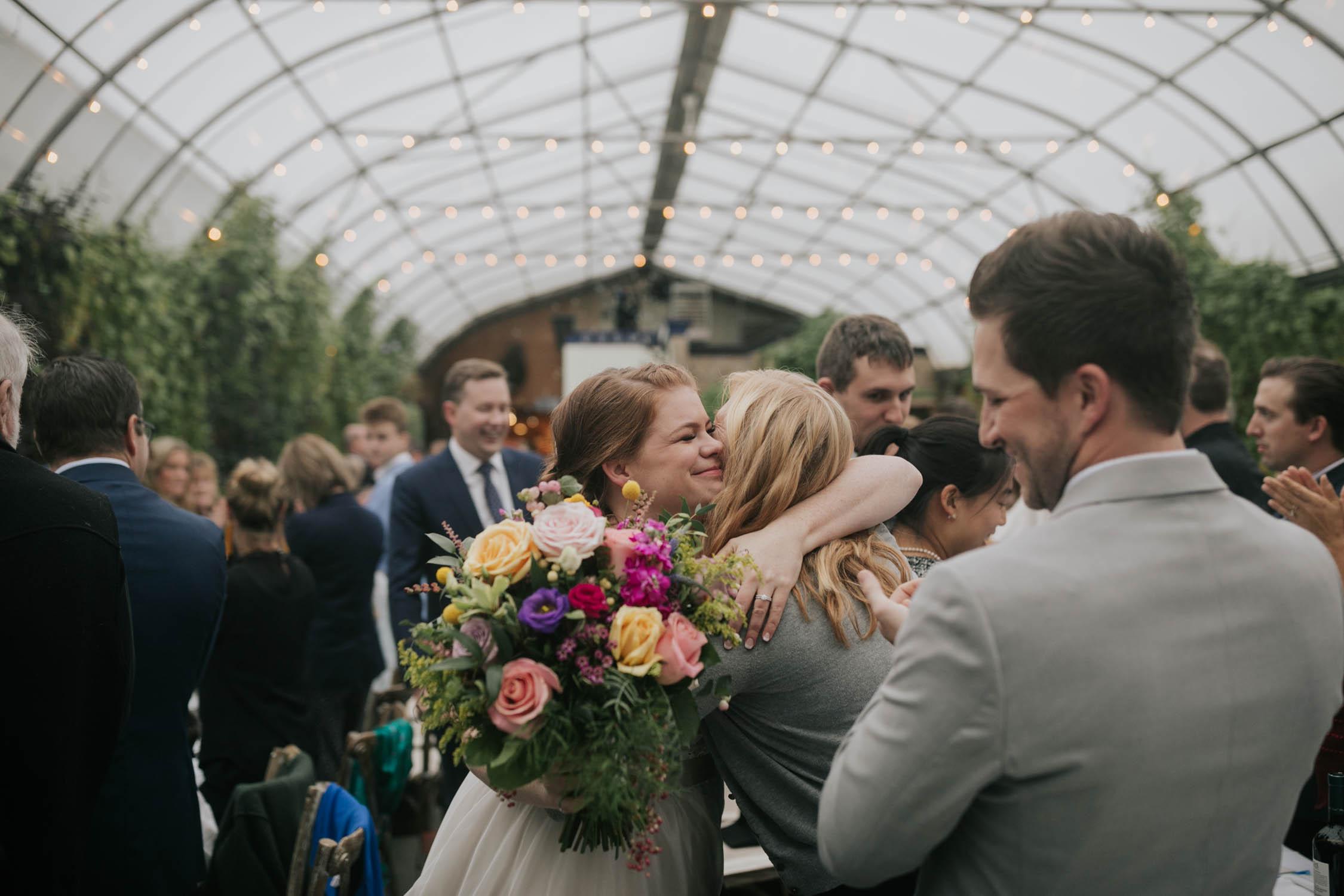 Bride hugs friend as bride and groom walk into wedding reception at Saskatoon Farm Wedding Venue in Calgary, Alberta.