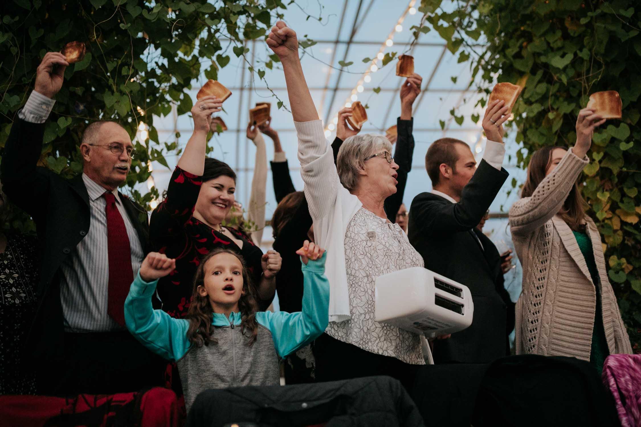 Fun wedding tradition of family singing a toast to happy couple at Saskatoon Farm Wedding Venue in Calgary, Alberta.