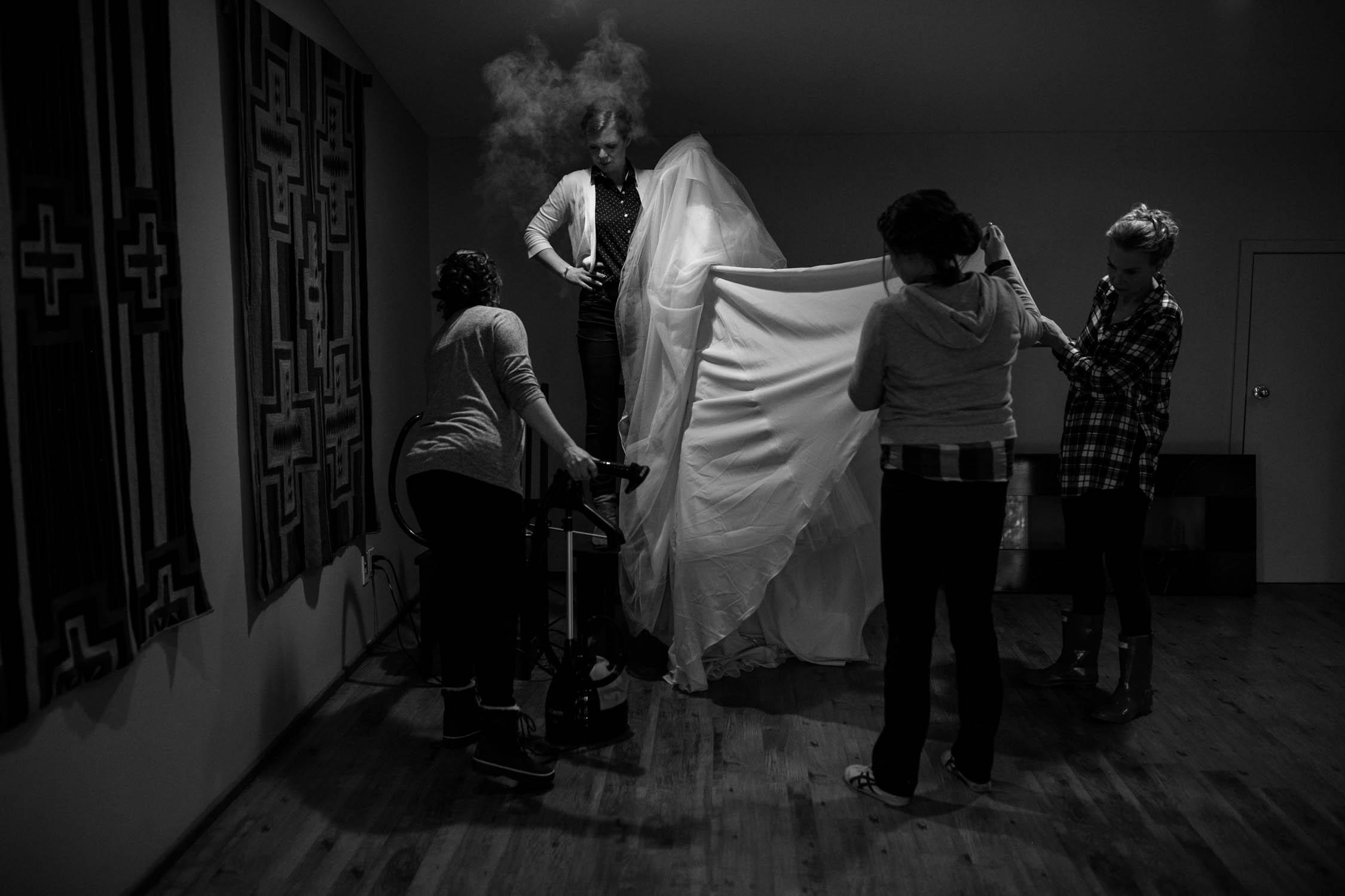 Candid getting ready photographs of bridesmaids' streaming wedding dress at Calgray wedding venue Saskatoon Farm