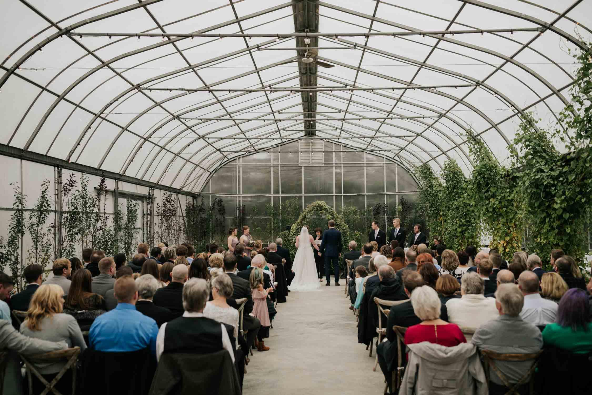 Wedding ceremony in the greenhouse at Saskatoon Farm Wedding Venue in Calgary, Alberta.