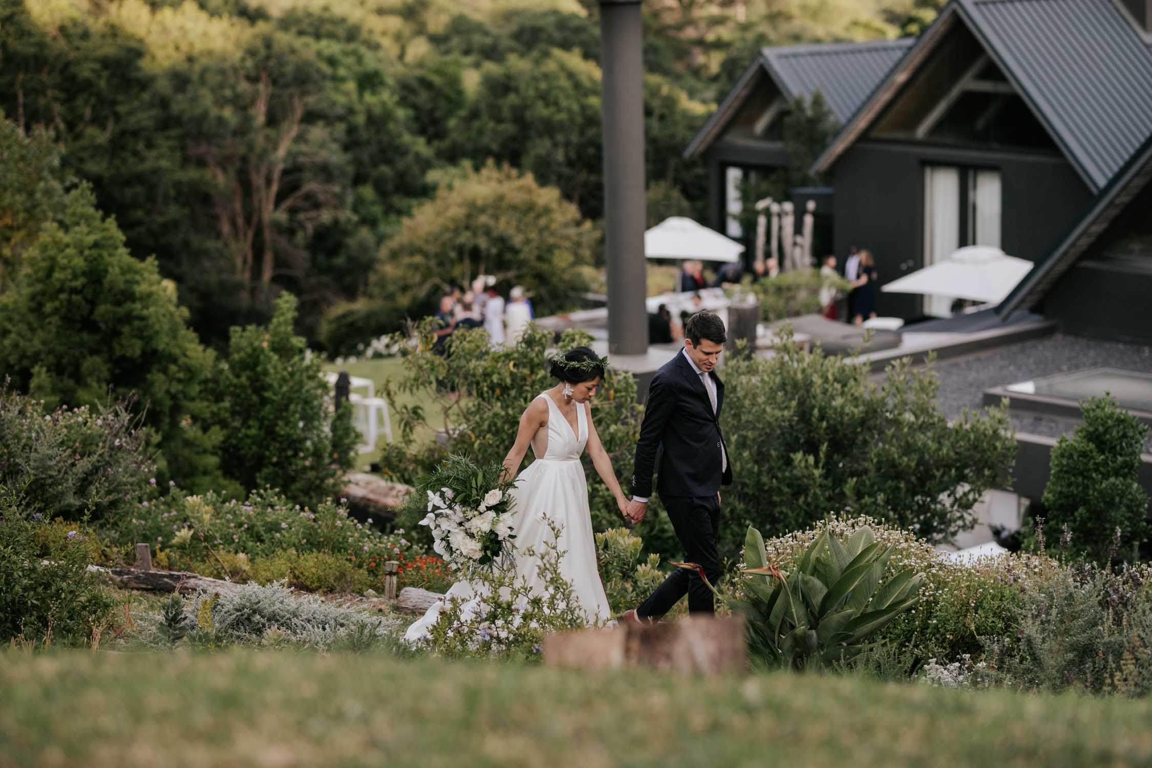 Bride And Groom Walking In Garden Hand In Hand