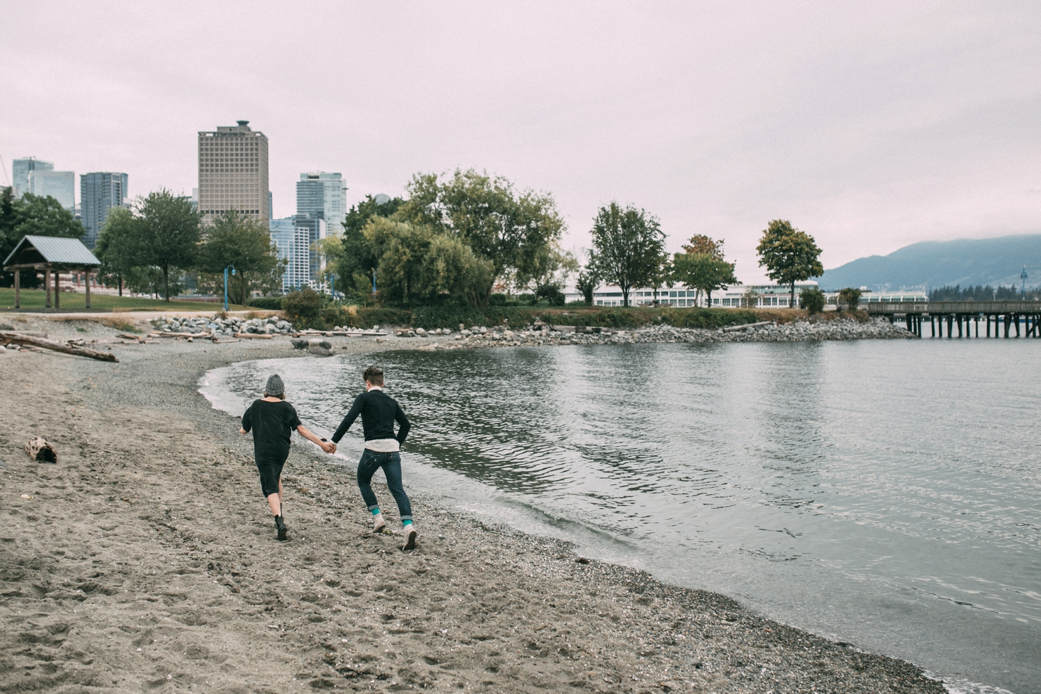 Engaged Couple In Love Run On Beach Stanley Park