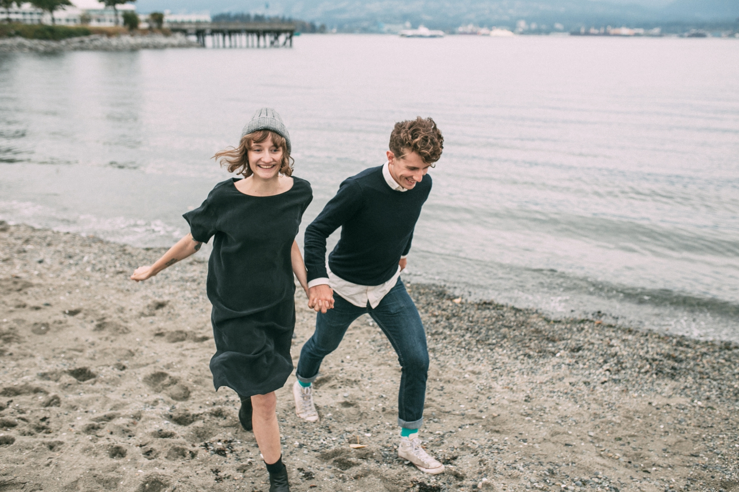 Couple holding hands running wild and free on the beach in Vancouver, BC