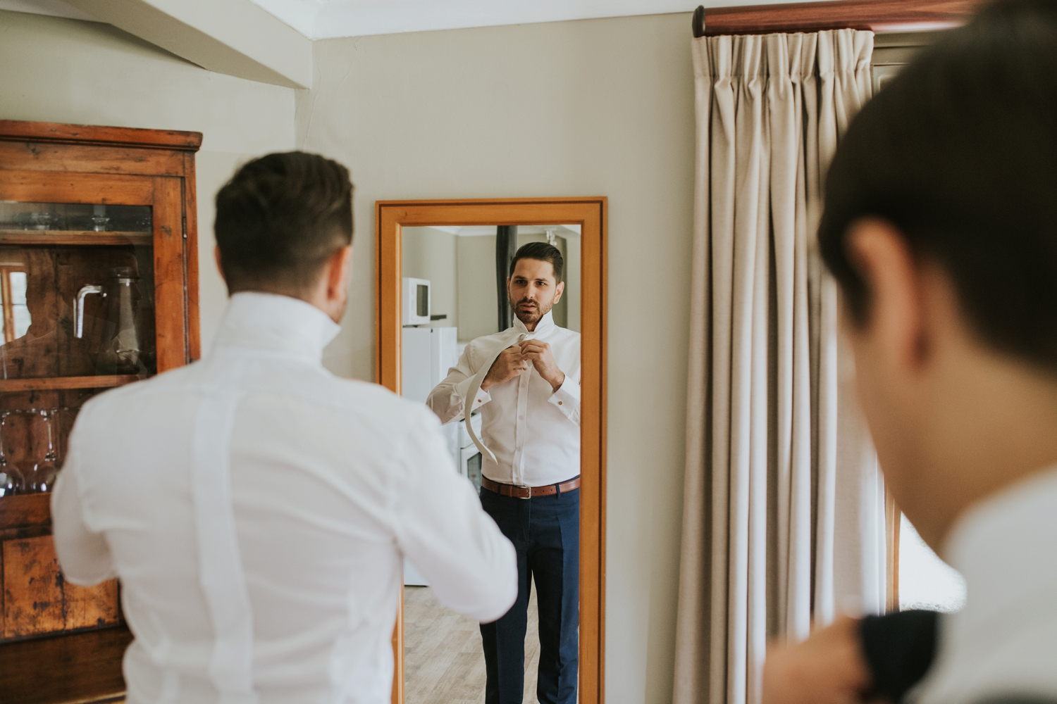 Groom Looking In Mirror Getting Ready Before Wedding Ceremony At Cecil Green Park House