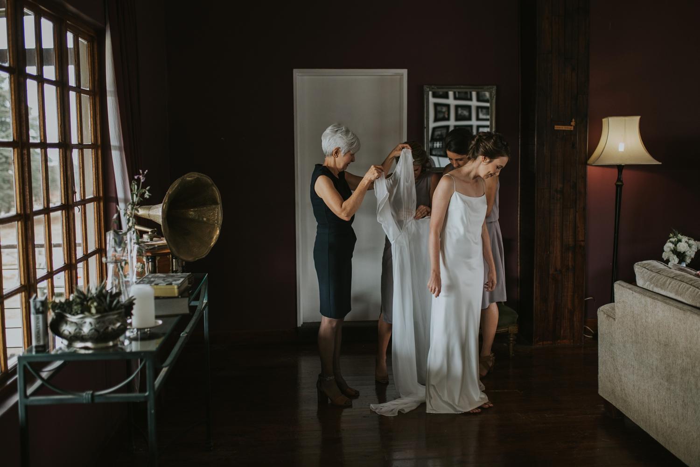 Mom Helping Bride Get Dressed In Simple Elegant Classic Layered Wedding Dress