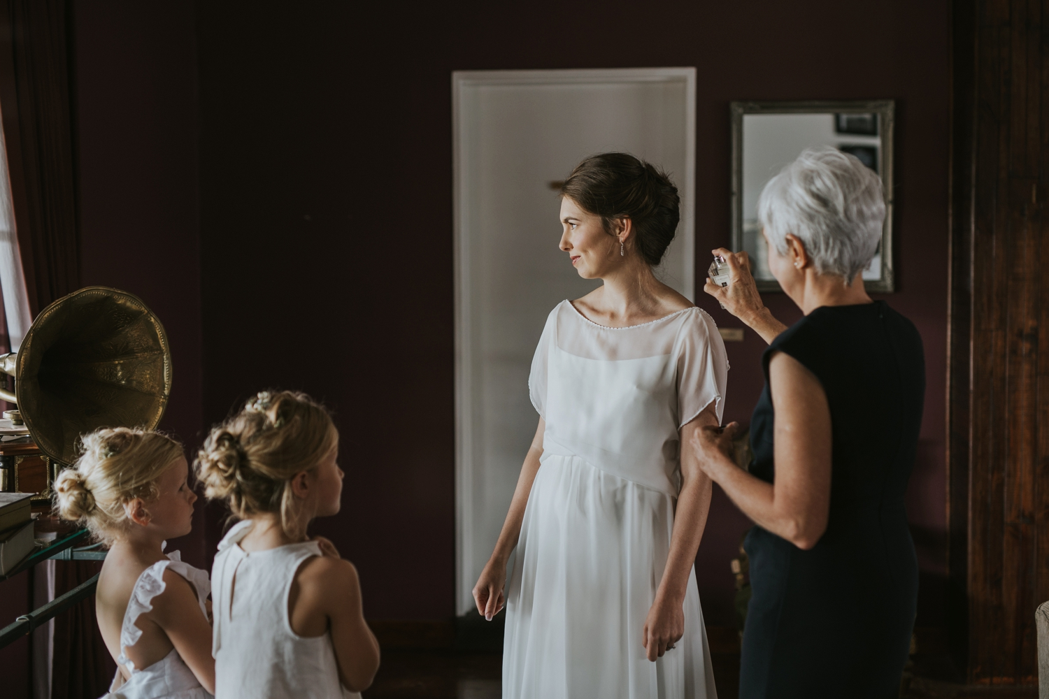 Mom Spraying Perfume On Bride Who Is Dressed In Simple Elegant Classic Layered Wedding Dress