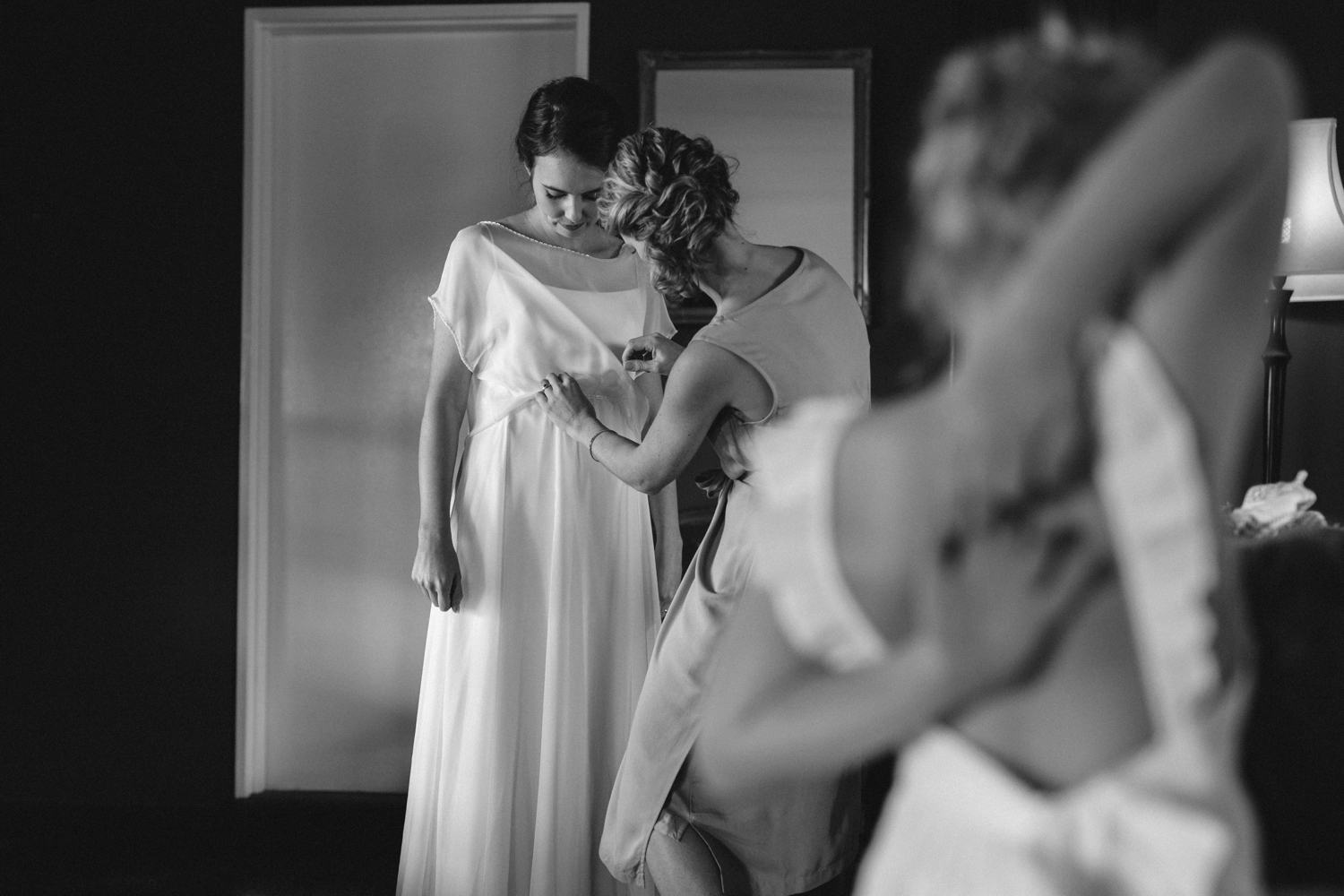 Bridesmaid Helping Bride Get Dressed In Simple Elegant Classic Layered Wedding Dress