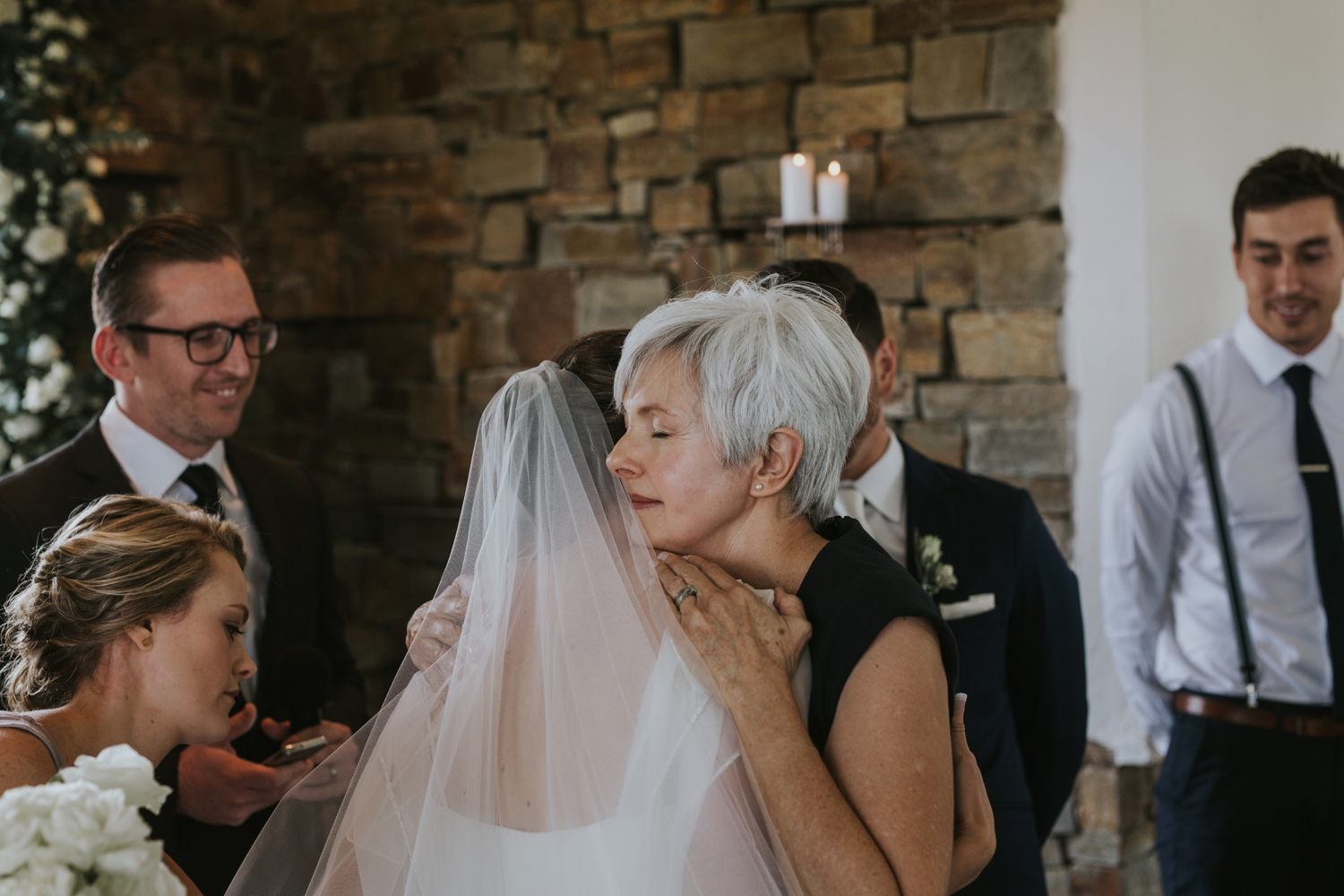 Candid and beautiful wedding moment of mother hugging her daughter after walking her daughter, the bride, down the aisle at Netherwood Wedding Venue in the Natal Midlands