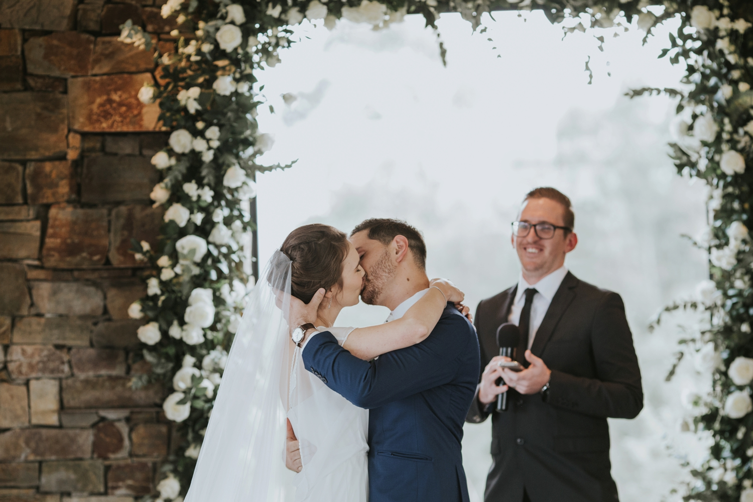 First kiss at Vancouver wedding ceremony surrounded by white roses
