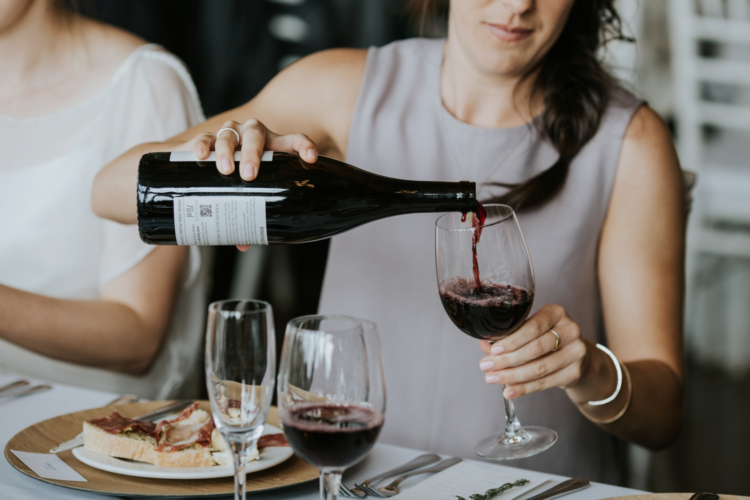 Wedding guest pouring red wine at Vancouver casual family style wedding lunch