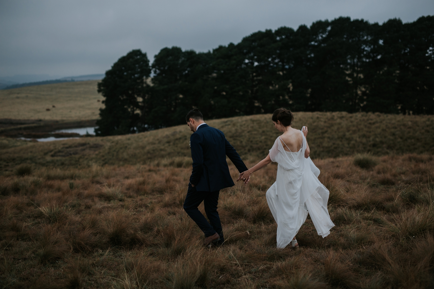 Bride and groom walk in an Iceland field during wedding photography session in Vancouver