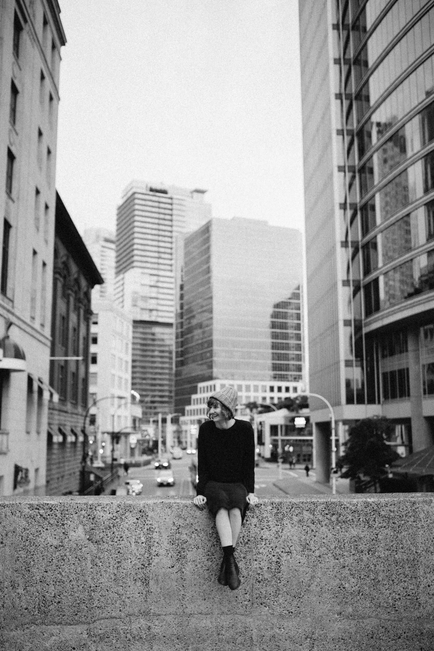 Candid and natural portrait of girl sitting on a wall laughing in Vancouver City
