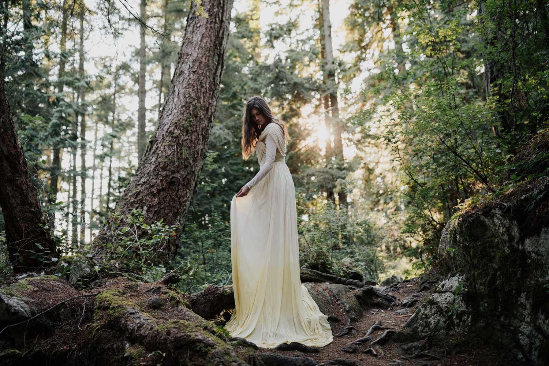Sunlight Shines Through Forest Onto Boho Vancouver Island Bride
