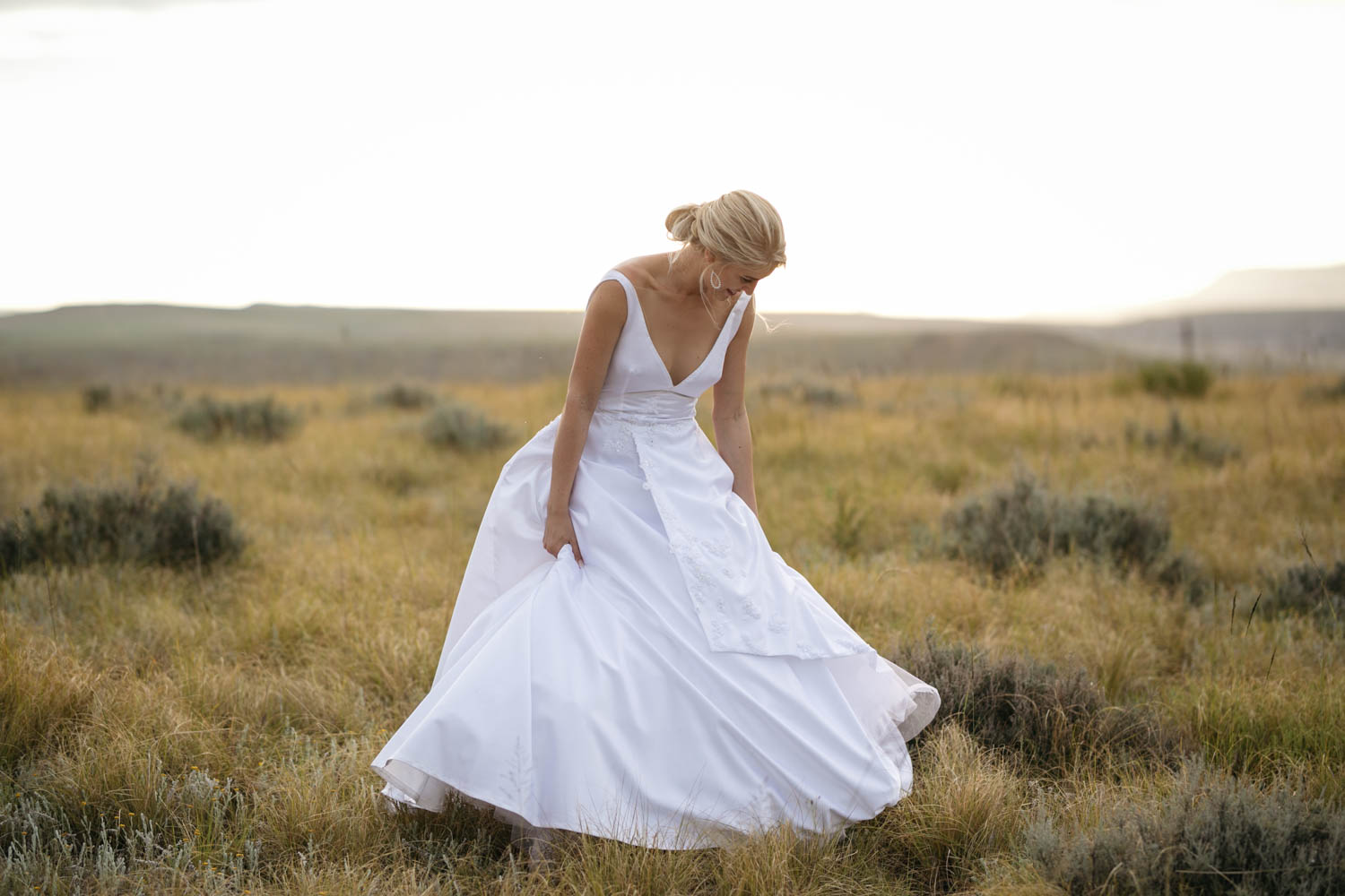 Bride Showing Off Classic White Silk Wedding Dress in Golden Field
