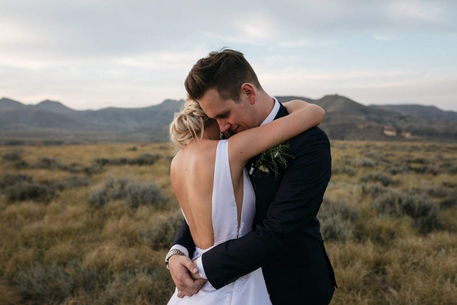Bride With Backless Modern Wedding Dress And Groom Candid Hug In Mountain Field In Whistler Vancouver