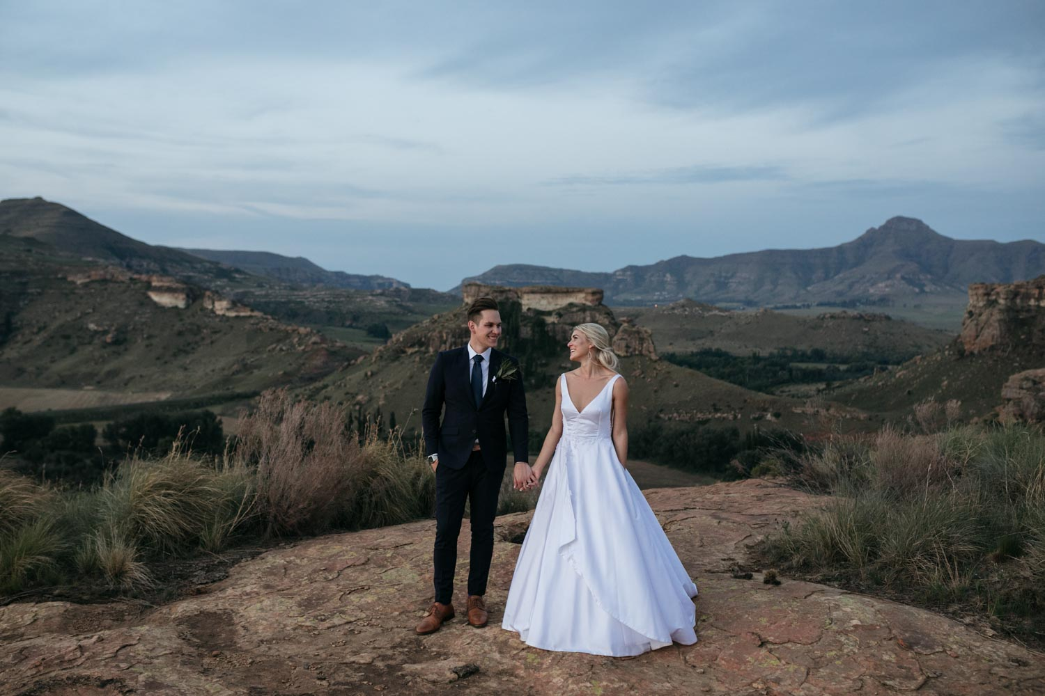 Epic Dusk Mountain Scene Bride and Groom Hold Hands