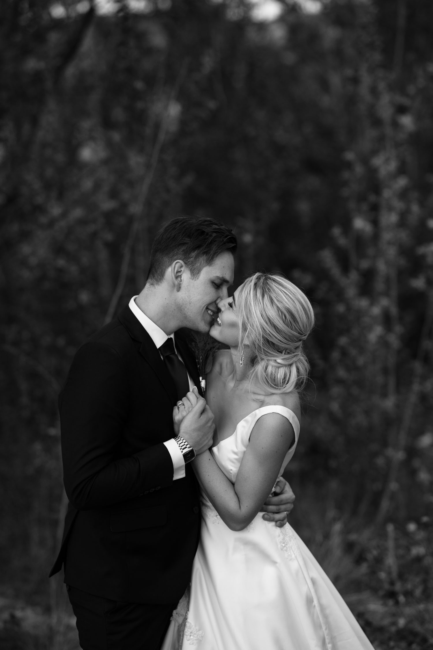 Candid Black And White Wedding Photo Of Bride And Groom Kiss And Hold Hands