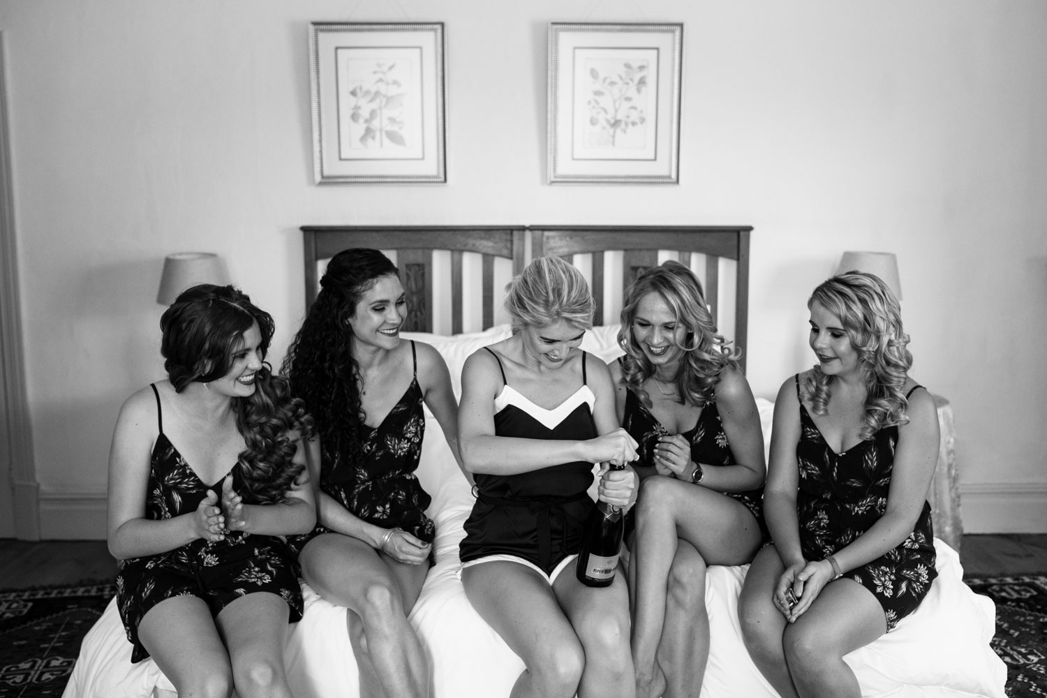 Bride And Bridesmaids Drink Champagne On Bed Wearing Cute Jumpsuits