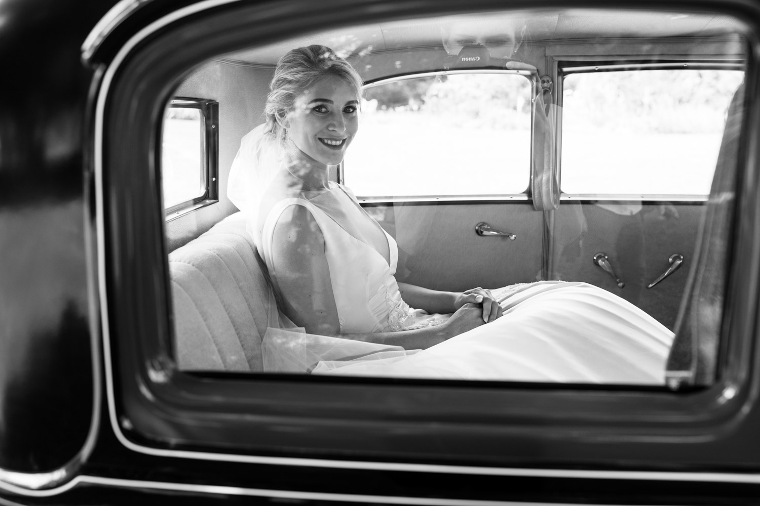 Bride In Vintage Car On The Way To Wedding Reception With Father