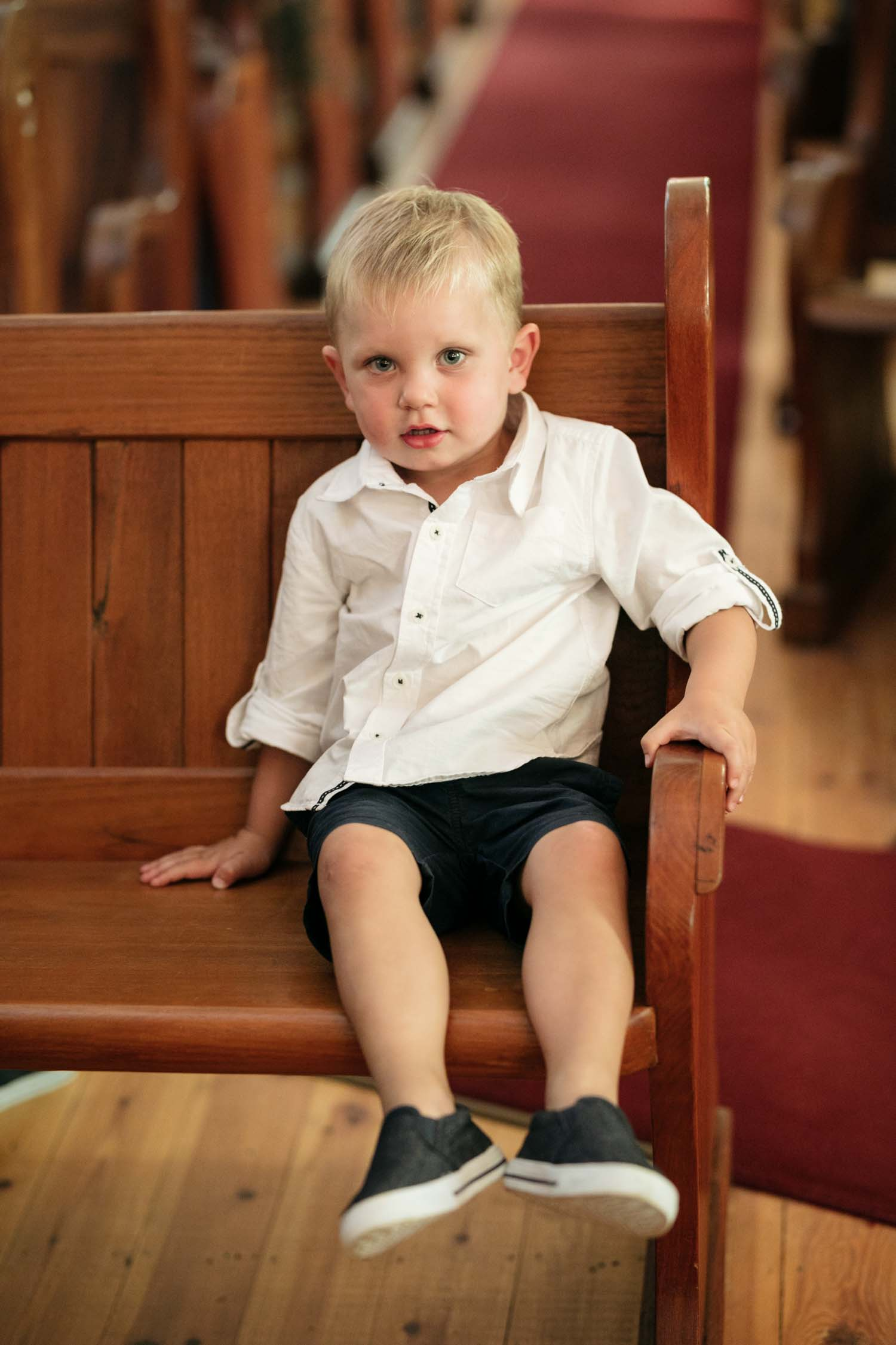 Page Boy Wearing Casual Wedding Outfit Blue Shorts White Rolled Up Shirt