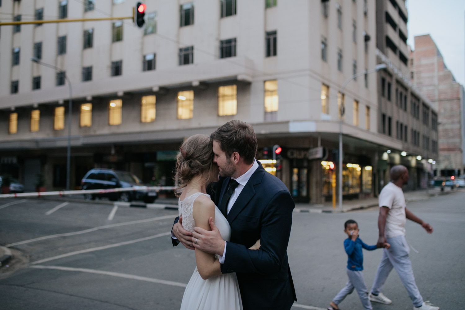 Alternative Wedding Photo Of Bride Holding Groom In Vancouver City As Pedestrians Walk Past