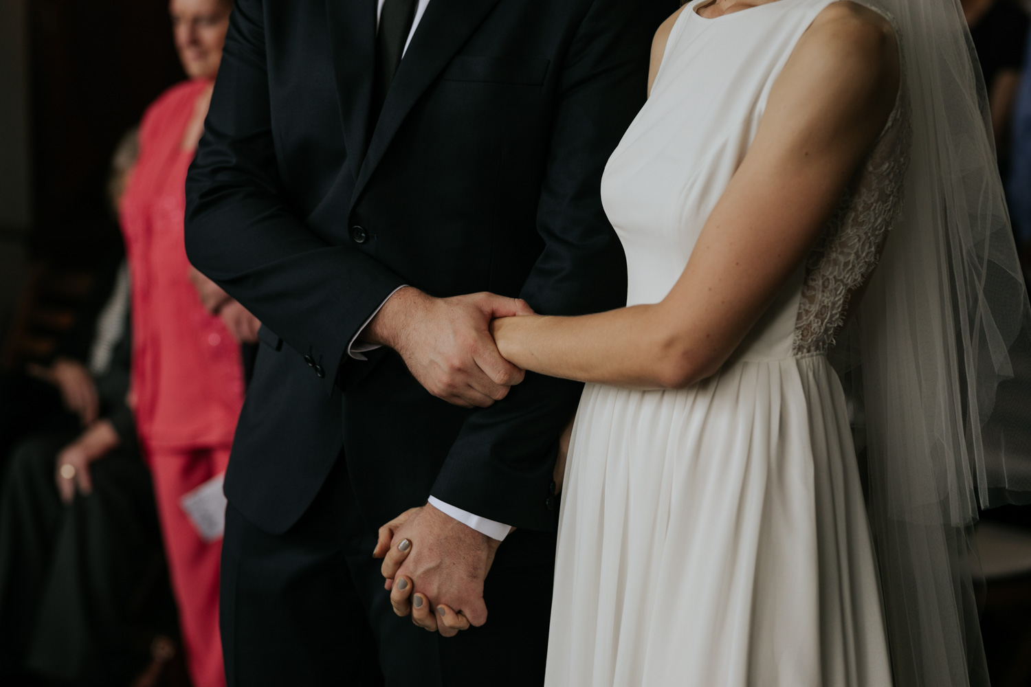 Bride And Groom Hold Hands In Wedding Ceremony
