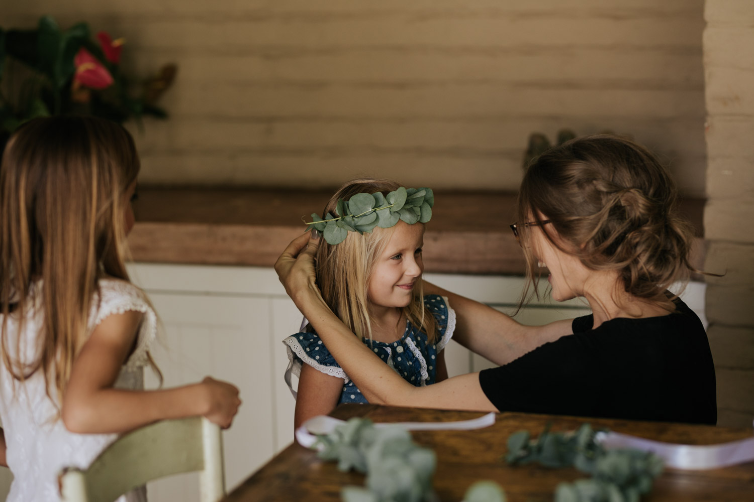 Bride Helps Flower Girl Put On Her Eucalyptus Leaf Flower Crown