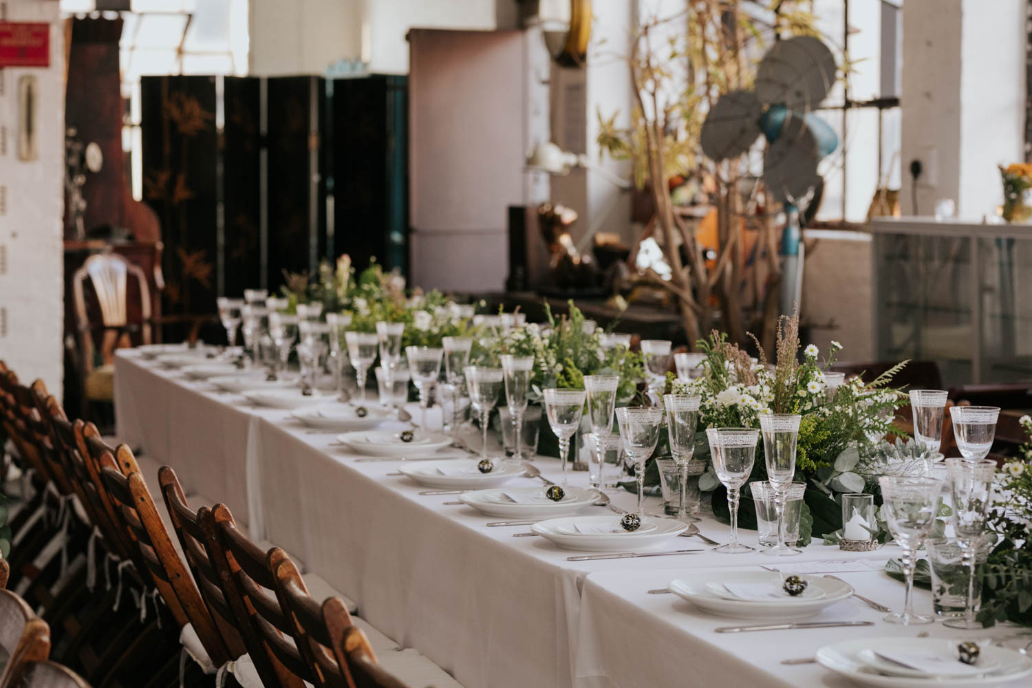 Simple White And Green Wedding Decor With Flowers, Eucalyptus Leaves, White Candles And Wooden Chairs.