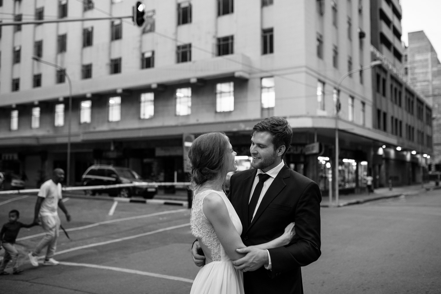 Bride Holds Groom In Vancouver City As Pedestrians Walk Past
