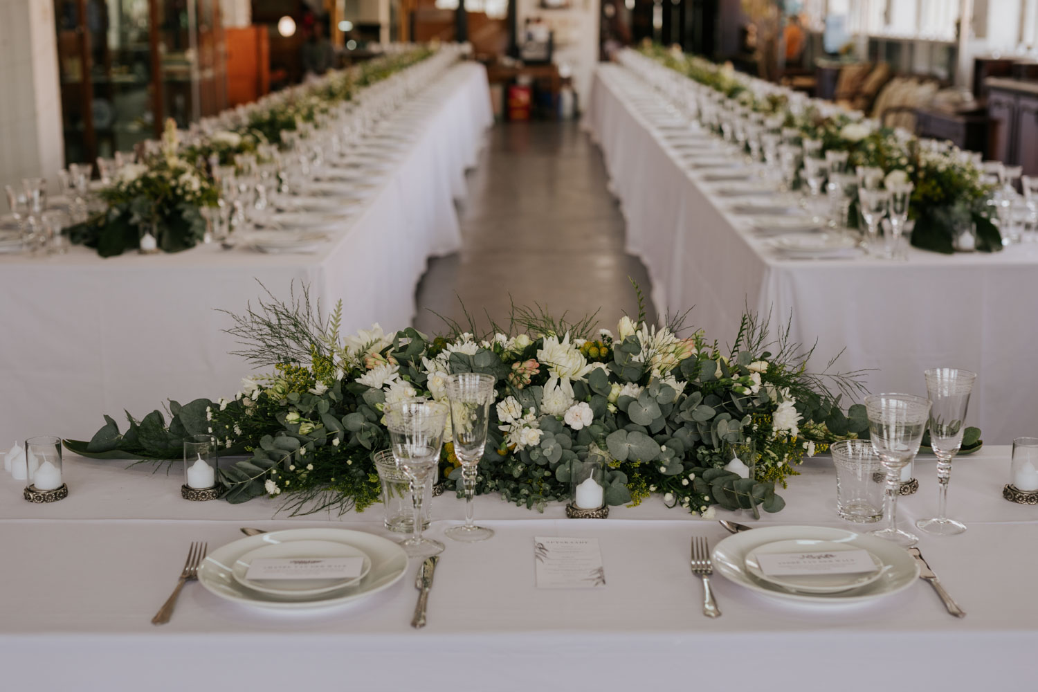Simple White And Green Wedding Decor With Flowers, Eucalyptus Leaves And Candles