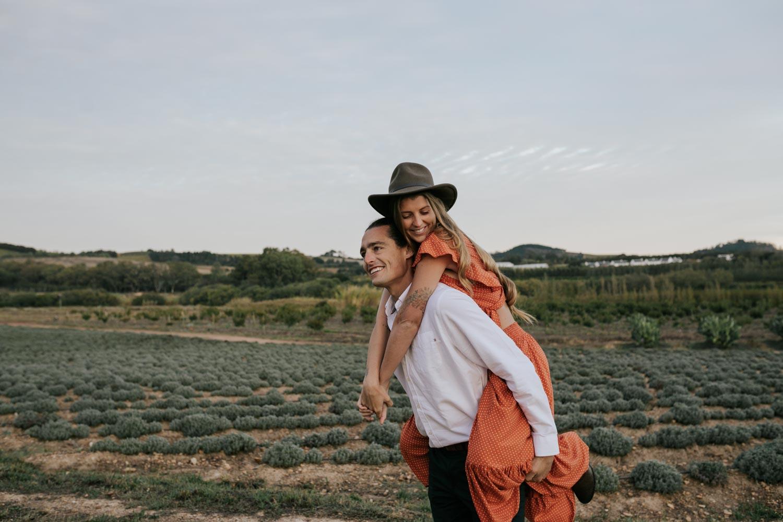 Boho Gypsy Couple Engagement Piggyback Ride In Babylonstoren Farm Fields Below Mountains