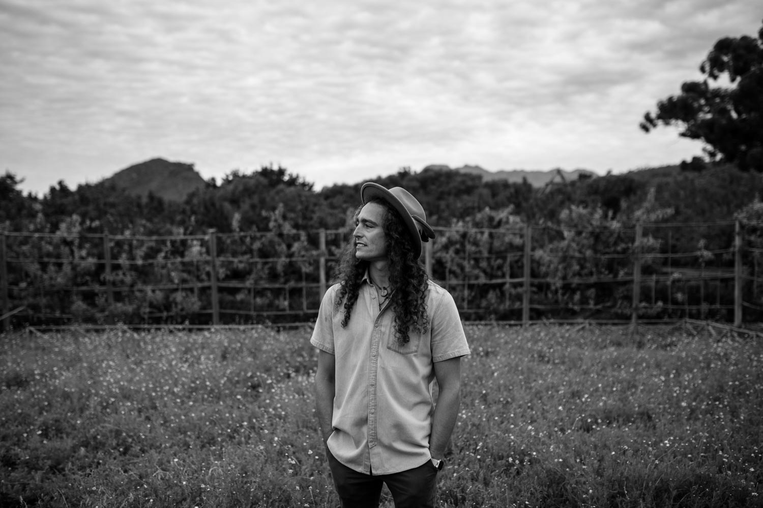 Boho Groom With Long Hair Wearing Felt Hat Stands in Camomile Field at Babylonstoren Cape Town Wedding Venue
