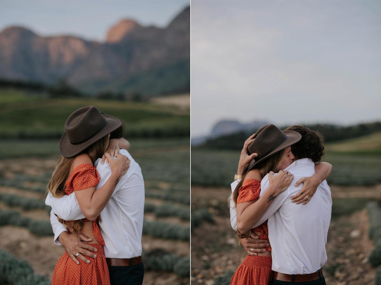 Boho Gypsy Couple Engagement Shoot Hug In Babylonstoren Farm Fields Below Mountains